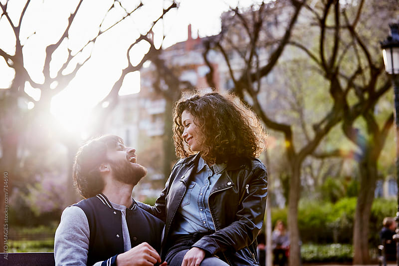 Cheerful Couple Sitting On Park Bench by ALTO IMAGES for Stocksy United