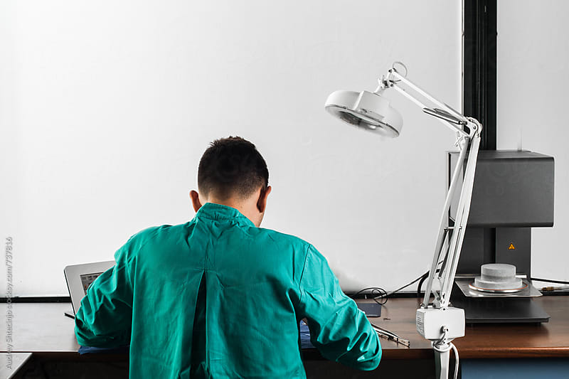 Look form behind on dental technician working in his ordination. by Audrey Shtecinjo for Stocksy United