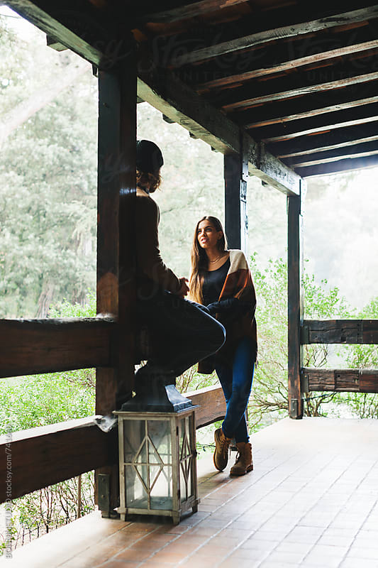 Couple talking in the porch of a rural home. by BONNINSTUDIO for Stocksy United
