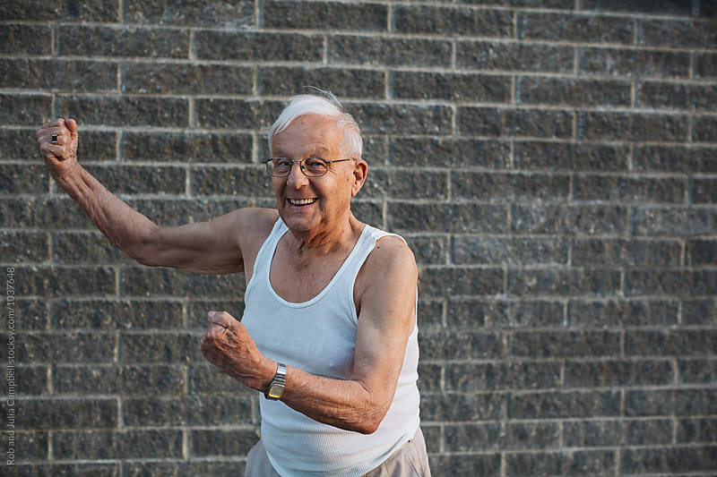 Happy, caucasian senior man outside on warm spring day - flexing muscles in tank top by Rob and Julia Campbell for Stocksy United