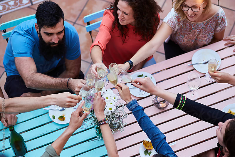 Group of cheerful friends toasting at table outdoor by Guille Faingold for Stocksy United