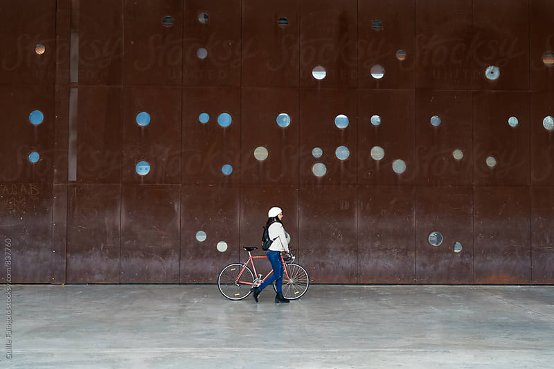 Young woman with a fixed gear bike walking in an urban scene by Guille Faingold for Stocksy United
