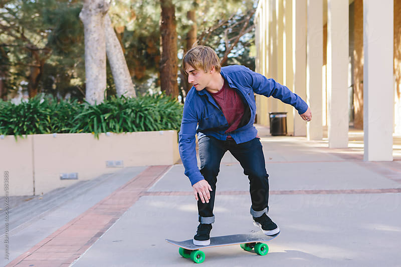 Young Man Skateboarding on Campus by Jayme Burrows for Stocksy United