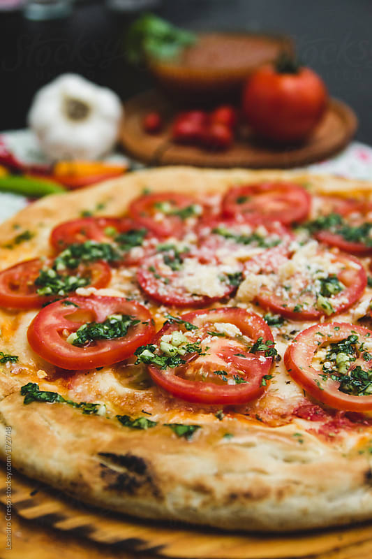 Tomato pizza with garlic by Leandro Crespi for Stocksy United