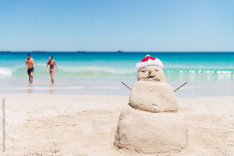 Large smiling sand snowman at the beach in Australia on Christmas Day by Angela Lumsden for Stocksy United