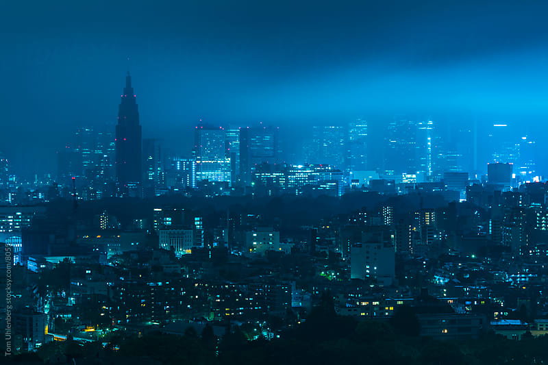 Moonlight Gleaming through Clouds and Fog over Shinjuku Skyline in Tokyo, Japan by Tom Uhlenberg for Stocksy United