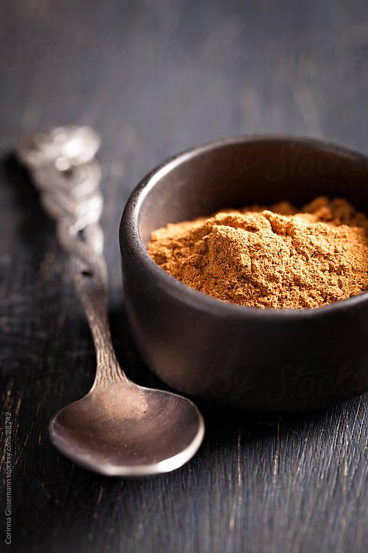 cinnamon powder in a black bowl  by Corinna Gissemann for Stocksy United