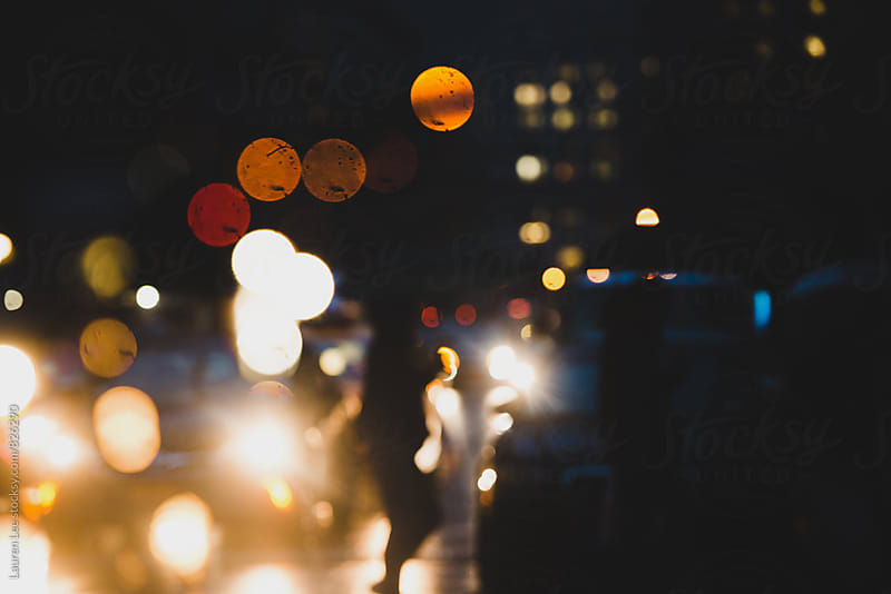 Traffic and people walking in rain at night by Lauren Naefe for Stocksy United