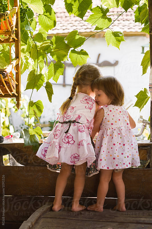 Two little girls playing together on the terrace by RG&B Images for Stocksy United
