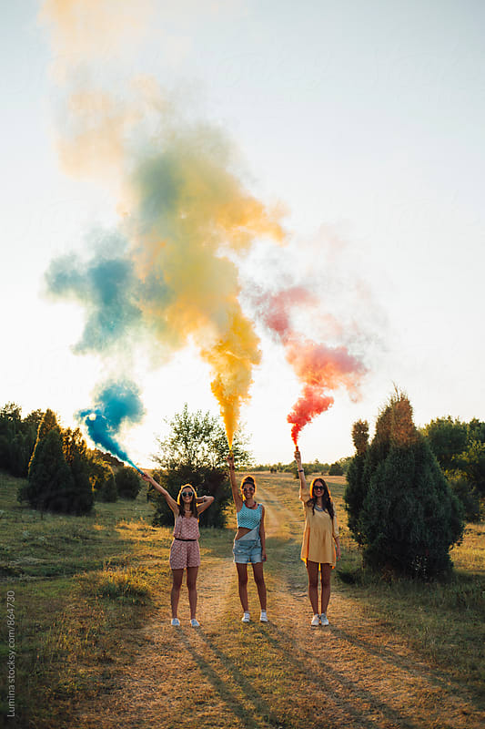 Happy Girls Holding Smoke Bombs by Lumina for Stocksy United