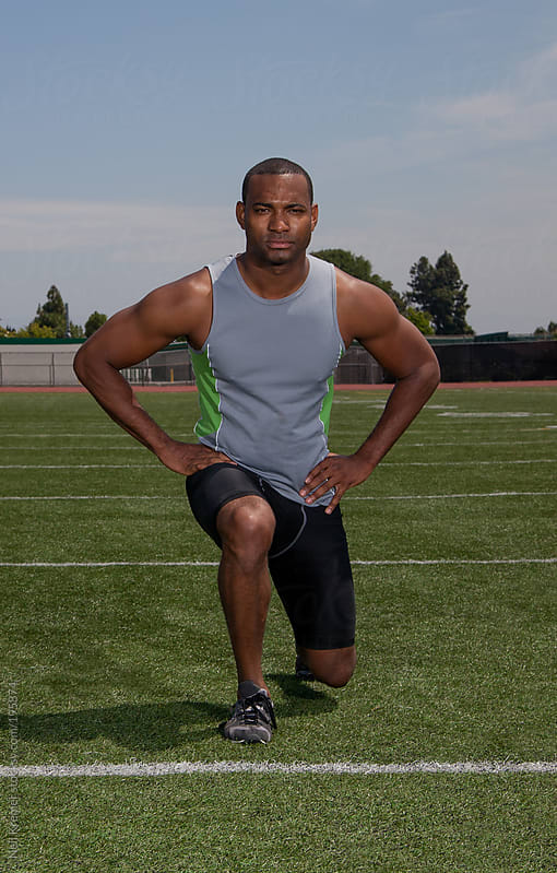 Man stretching for a track and field event by Neil Kremer for Stocksy United