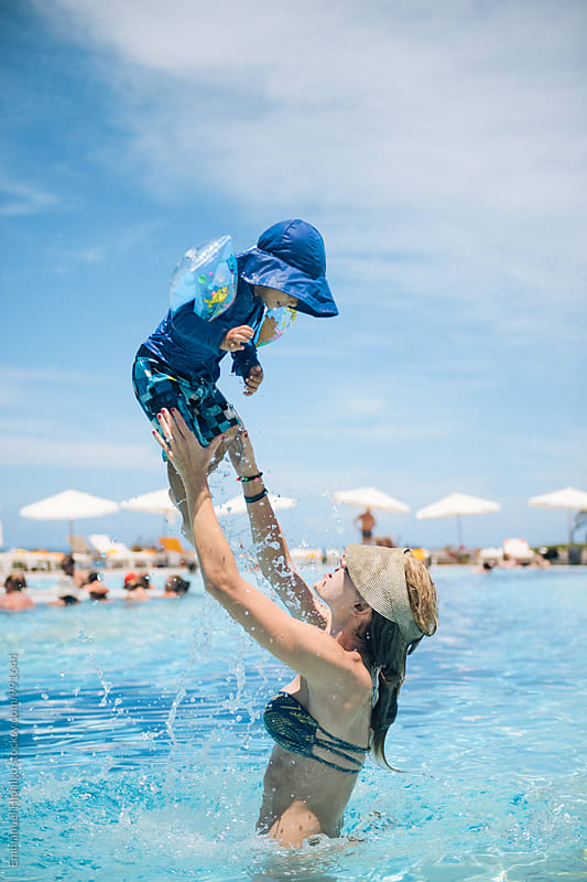 Mom lifts up her son high in the air at a resort pool in Bahia, Brazil by Emmanuel Hidalgo for Stocksy United