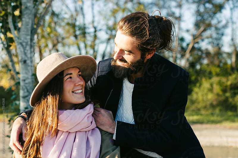 Hipster couple smiling in the forest. by BONNINSTUDIO for Stocksy United