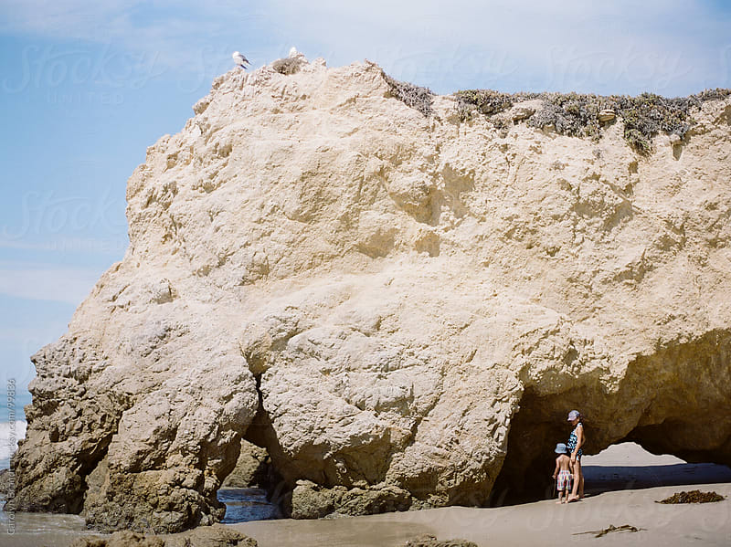 children exploring the beach rocks in Malibu, California by Carolyn Brandt for Stocksy United