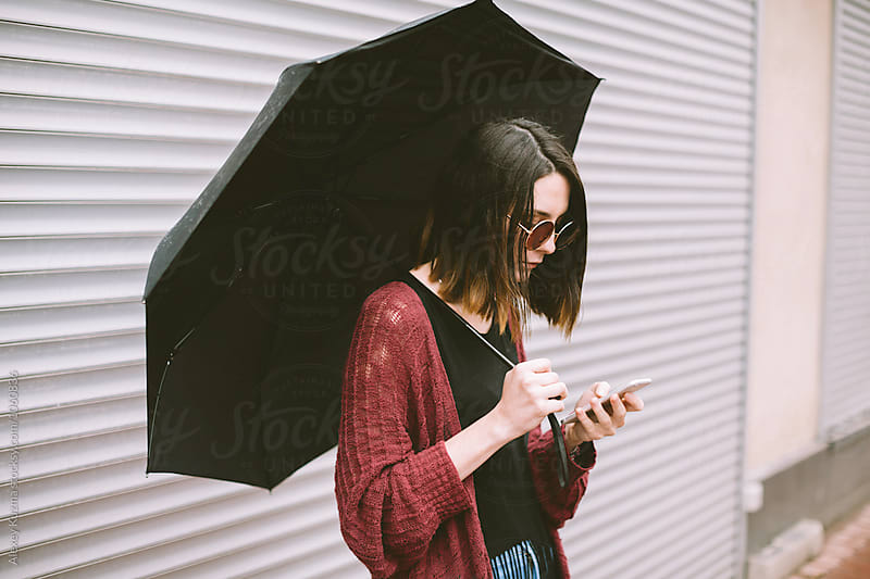 portrait of real young woman  using her smartphone on the street . rainy day. by Vesna for Stocksy United