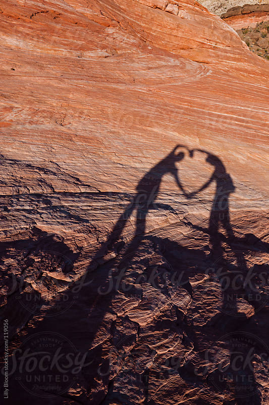 Shadow of two lovers forming a heart with their arms by Lilly Bloom for Stocksy United