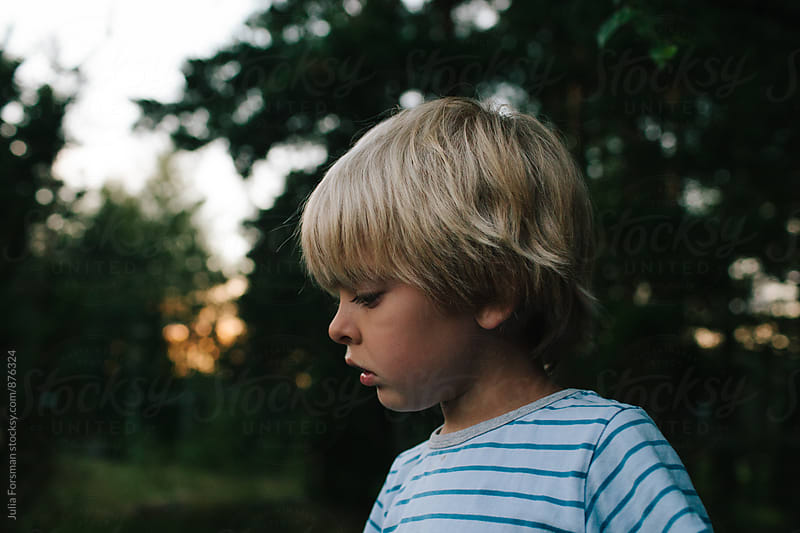 Profile of blonde child in a rural setting at dusk. by Julia Forsman for Stocksy United