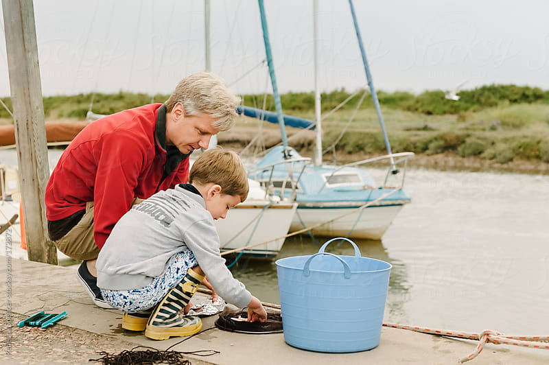 Young boy & Dad checking net for crabs. by Rebecca Spencer for Stocksy United