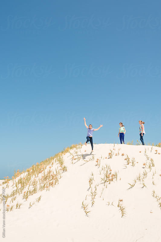 jumping the sand dunes by Gillian Vann for Stocksy United