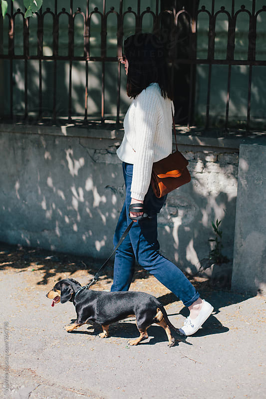 Woman walking her dog by VeaVea for Stocksy United