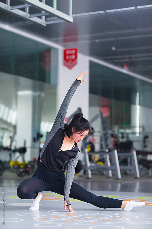 young asian woman stretch her body in the gym by Bo Bo for Stocksy United