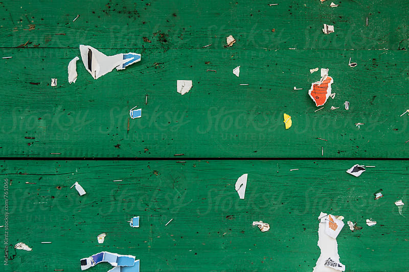 Green wooden background with remains of information leaflets by Melanie Kintz for Stocksy United