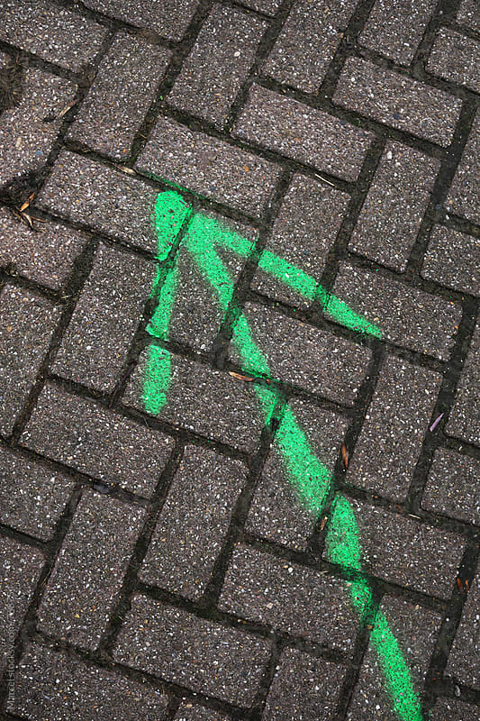 Green arrow painted on a brick road, pointing forwards by Marcel for Stocksy United