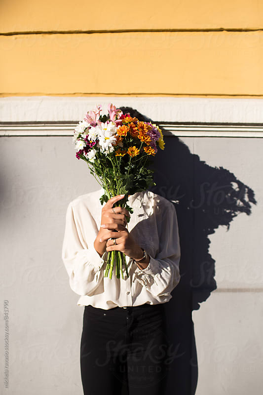 Woman with face covered with a bouquet of flowers by michela ravasio for Stocksy United