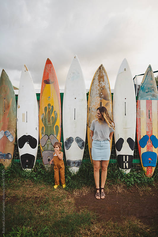 Young, stylish mom and cute toddler daugher    together in front of surf board fence by Rob and Julia Campbell for Stocksy United