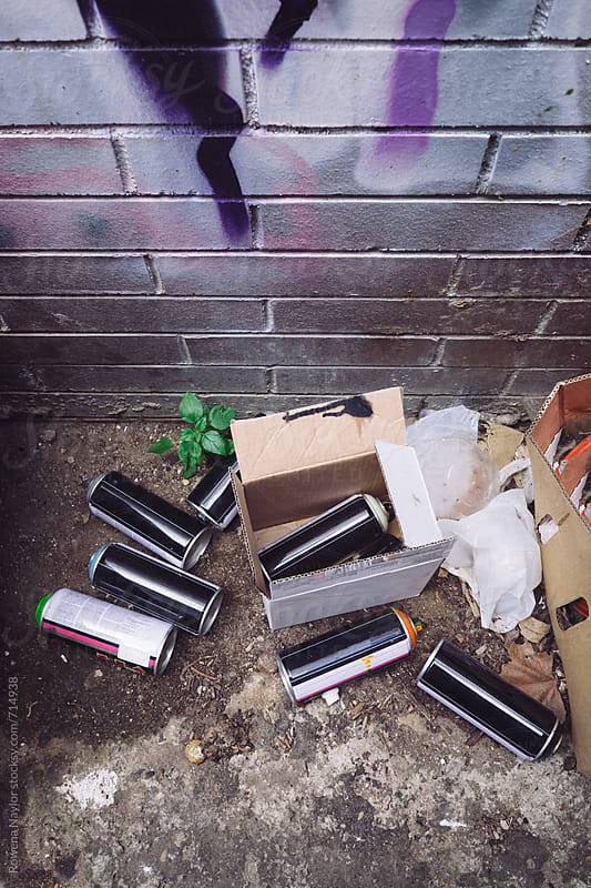 Empty aerosol paint cans left by street artists in laneway by Rowena Naylor for Stocksy United