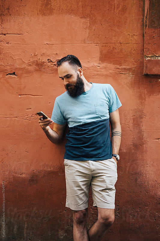 Handsome Bearded Man Using Phone by Katarina Radovic for Stocksy United