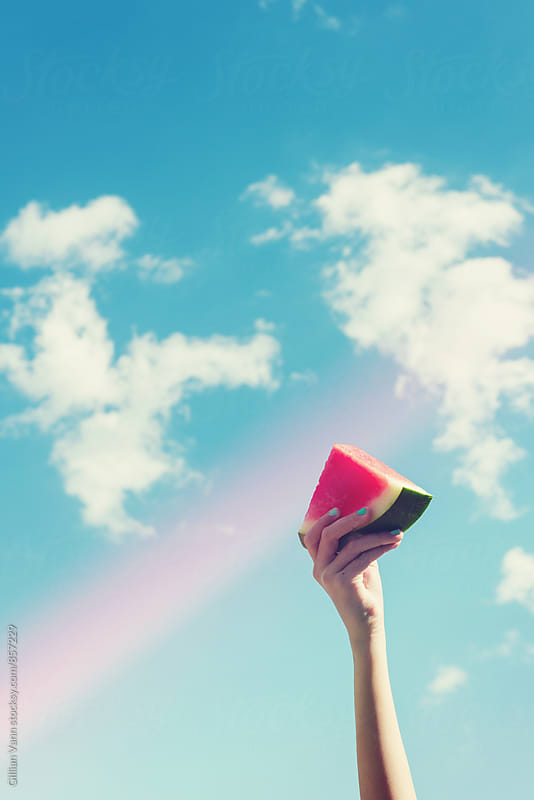 watermelon in hand, against a blue sky, with a light leak by Gillian Vann for Stocksy United