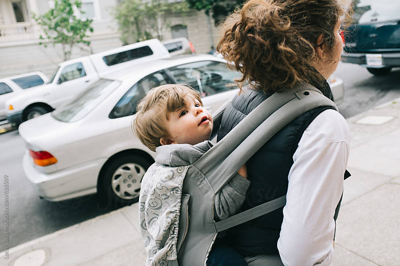 Mother carries her sone on her back in the city. by Lucas Saugen for Stocksy United