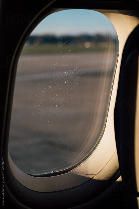Airplane Window With Some Frost Left From the Flight by Nemanja Glumac for Stocksy United