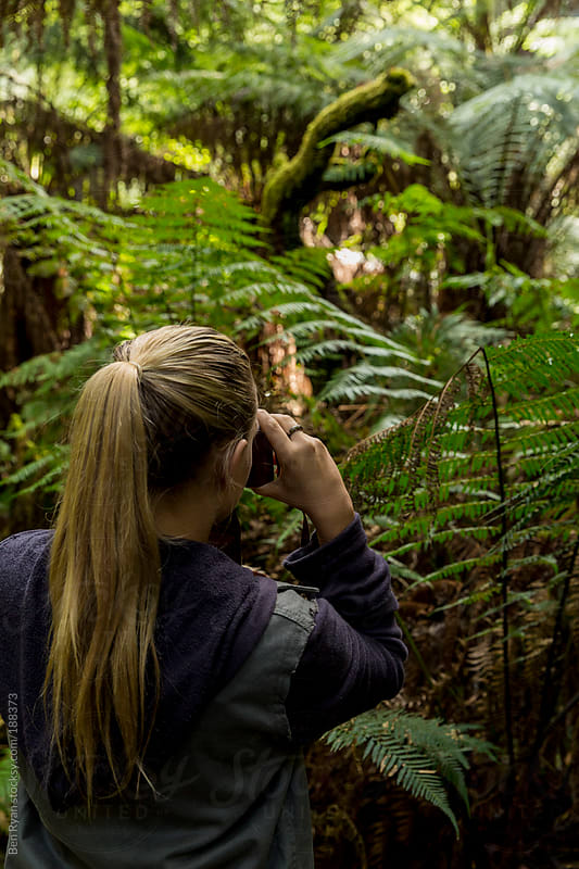 Young woman photographing Australian bush by Ben Ryan for Stocksy United