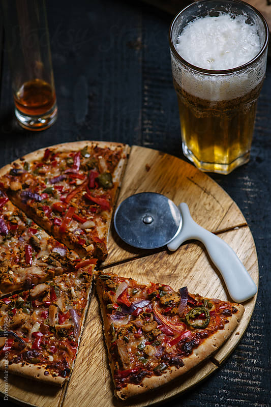 Pizza and beer. by Darren Muir for Stocksy United