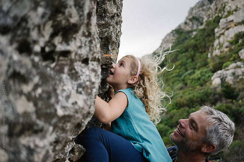 Dad and daughter rock climbing by Bruce and Rebecca Meissner for Stocksy United