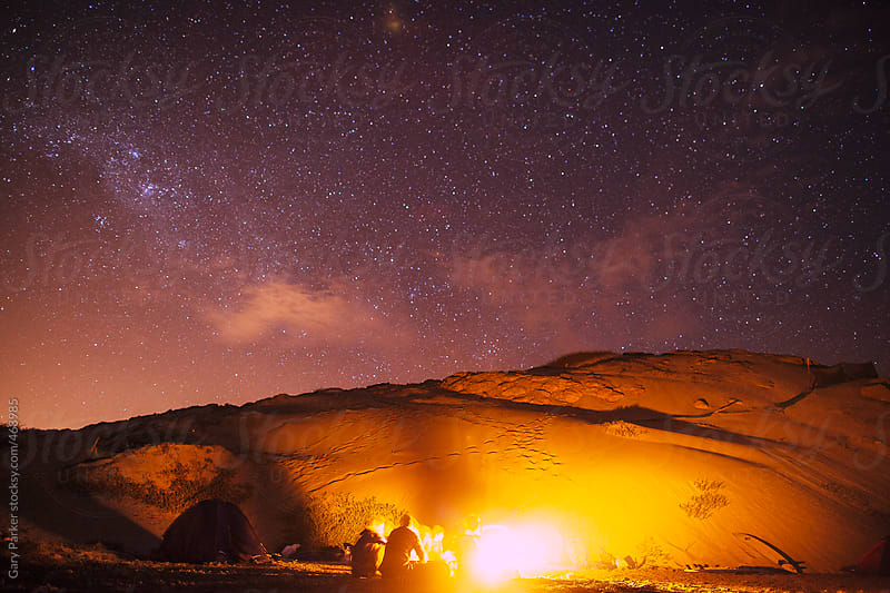 Campfire under the stars on a beach surrounded by sand dunes by Gary Parker for Stocksy United