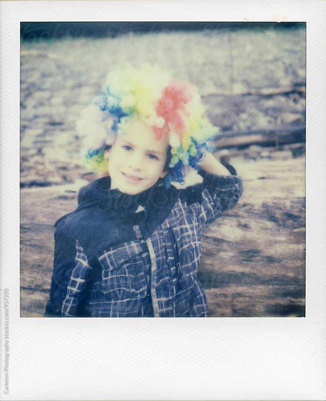 Boy in rainbow clown wig takes a break by leaning against a log by Carleton Photography for Stocksy United