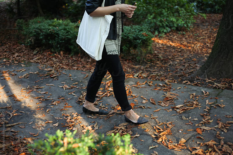 Female person walking on a path with autumn leafage  by VeaVea for Stocksy United