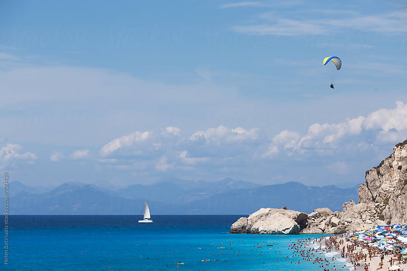 Beach with Sunbathers, Sailboat and Paragliding by Helen Sotiriadis for Stocksy United