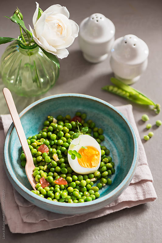Stewed peas and boiled egg in a light blue bowl by Laura Adani for Stocksy United