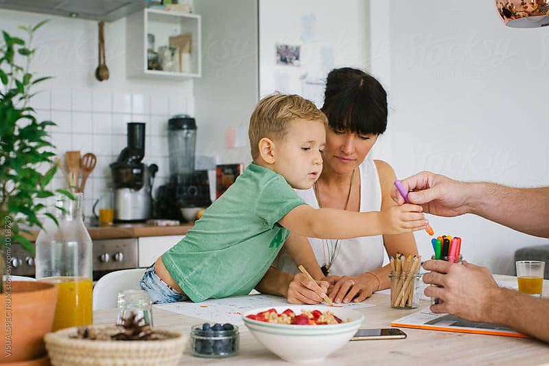 Family at Home - Small Blond Caucasian Boy Painting With Parents at Kitchen Table by Julien L. Balmer for Stocksy United