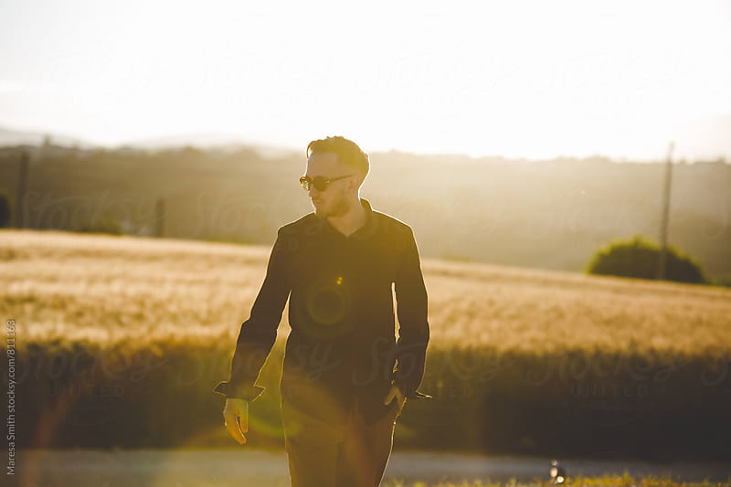 A man wearing a black shirt walking a country path at golden hour by Maresa Smith for Stocksy United