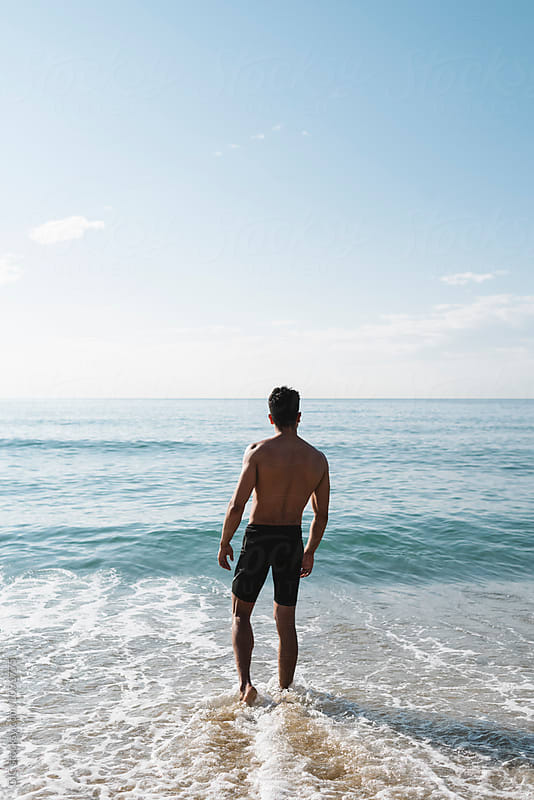 Young man standing against the sea by Simone Becchetti for Stocksy United