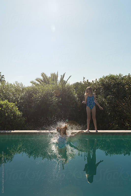 one girl jumps in the pool as other laughs by Gillian Vann for Stocksy United