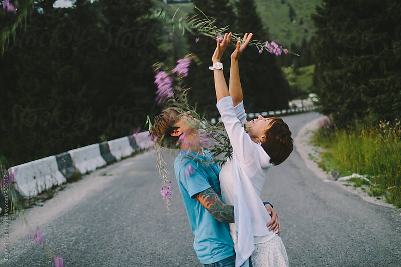 Young couple playing with flowers on the mountain road by Evgenij Yulkin for Stocksy United