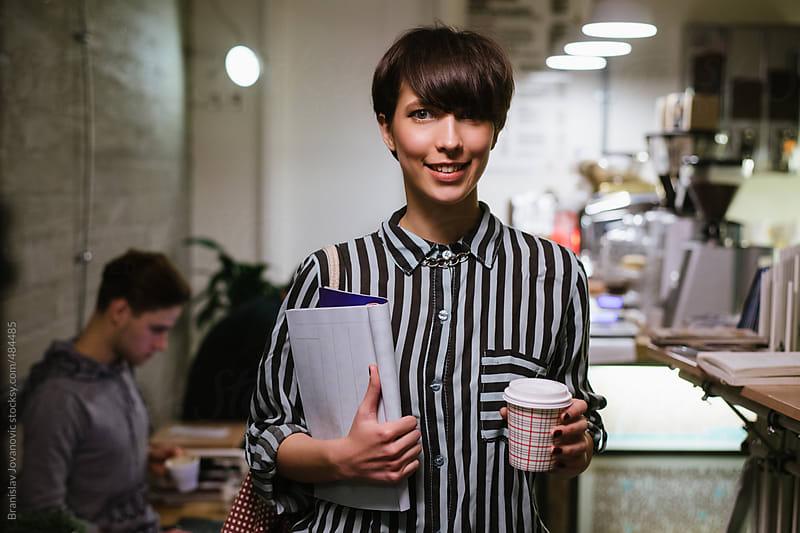 Stylish woman holding newspaper and take out coffee by Branislav Jovanović for Stocksy United
