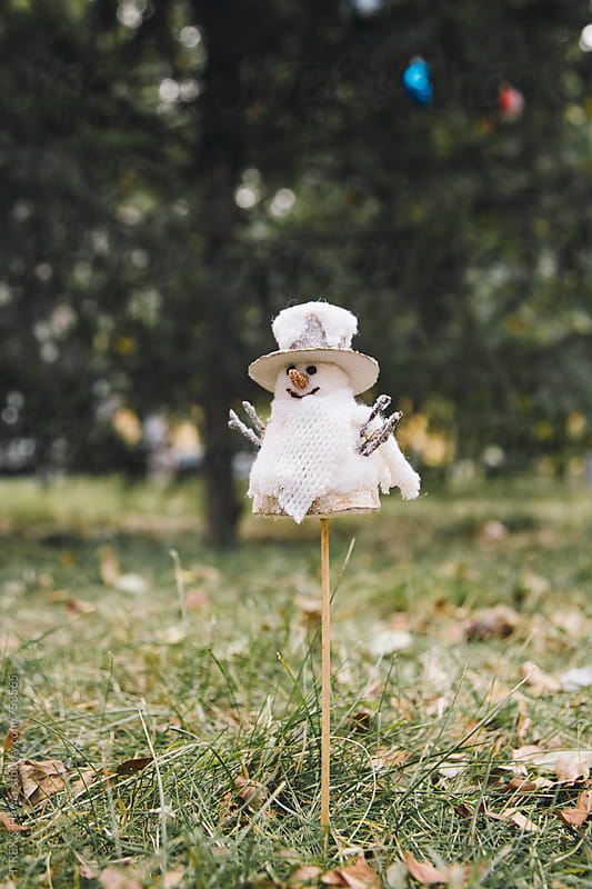 Snowman on stick standing on grass by Danil Nevsky for Stocksy United