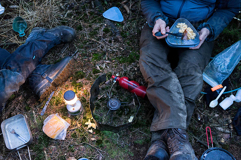 two hikers sitting on the forest floor eating dinner. by Tristan Kwant for Stocksy United